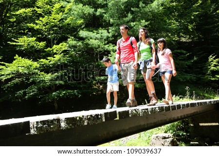 Family walking on a bridge in mountain forest - stock photo