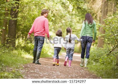 Family walking on path holding hands - stock photo