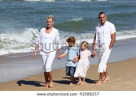 Family walking on the beach - stock photo