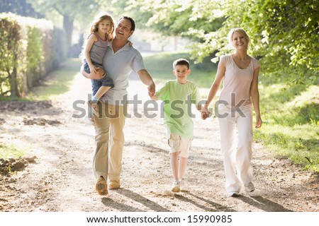 Family walking outdoors holding hands and smiling - stock photo