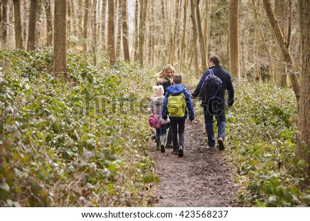 Family walking through a wood, back view, mum turning round - stock photo