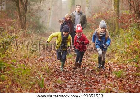 Family Walking Through Winter Woodland - stock photo