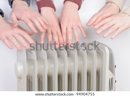 Family warm up hands over electric heater - stock photo