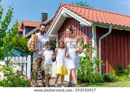 Family was shopping, now carrying groceries from car to house in paper bags - stock photo