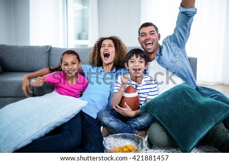 Family watching american football match on television at home - stock photo