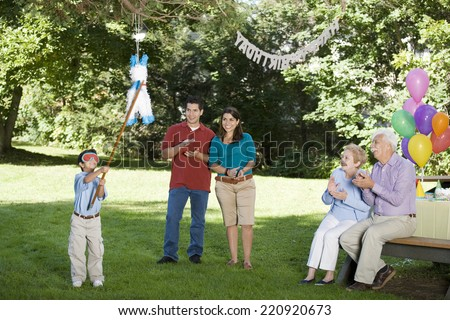 Family watching Hispanic boy hitting pinata at birthday party - stock photo