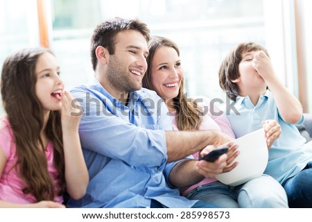 Family watching TV and eating popcorn - stock photo