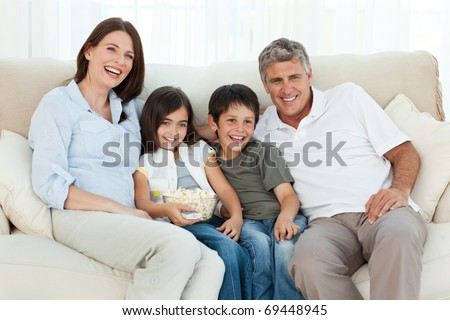 Family watching tv while they are eating popcorn - stock photo