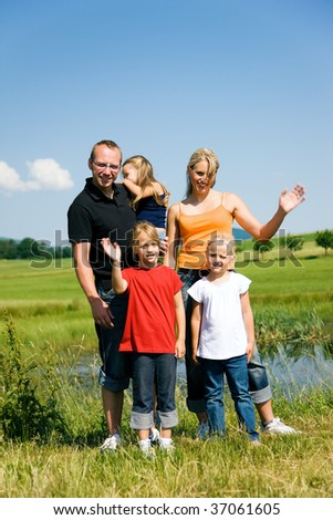 Family waving their hands at the camera - stock photo