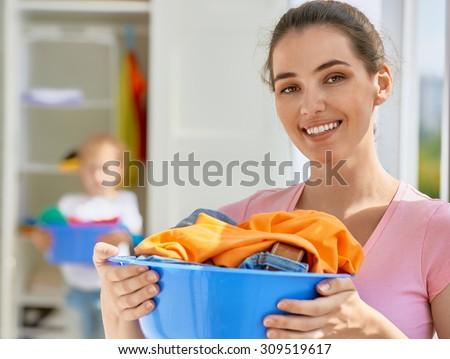 family with a basin full of laundry - stock photo