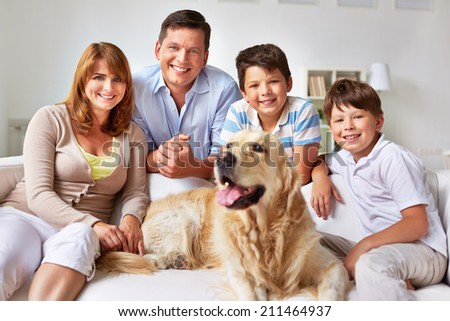 Family with a dog posing on sofa - stock photo
