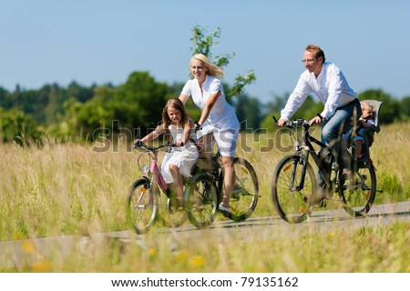 Family with baby and girl child having a weekend excursion on their bikes on a summer day in beautiful landscape - stock photo