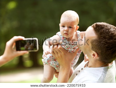 Family with baby In Park taking selfie by mobile phone - stock photo