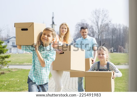Family with cardboard boxes moving into new house - stock photo