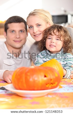 Family with carved pumpkin - stock photo