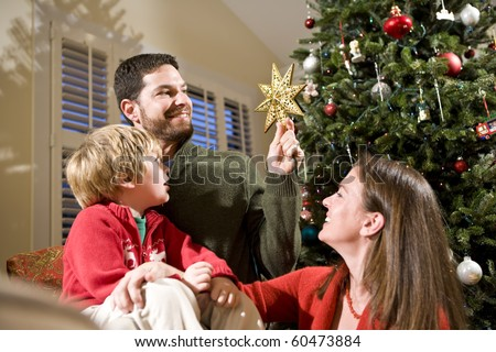 Family with child by Christmas tree, dad holding star - stock photo