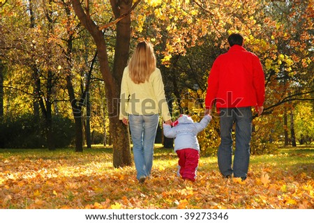 Family with child go in autumn park - stock photo
