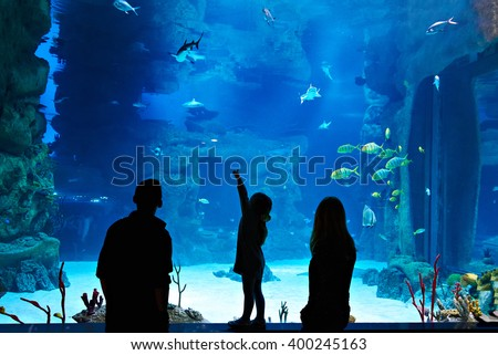 Family with child visitors a large oceanarium - stock photo