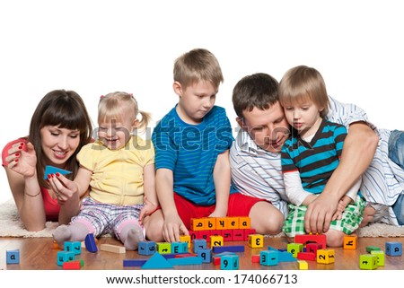 Family with children are playing on the floor with blocks - stock photo