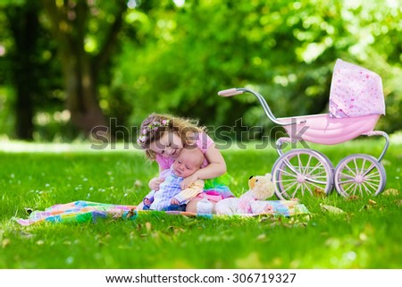 Family with children enjoying picnic outdoors. Little girl playing with newborn baby brother in summer park. Child playing with toy stroller. Sister kissing new born sibling. Kids birthday party. - stock photo
