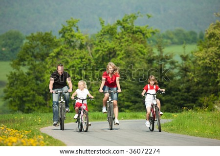 Family with children having a weekend excursion on their bikes on a summer day - stock photo