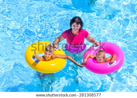 Family with children on beach ring in swimming pool. Summer outdoor. - stock photo