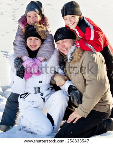 Family with children on snow in winter - stock photo
