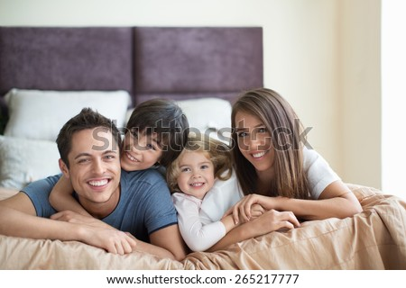 Family with children on the bed - stock photo