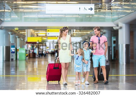 Family with children with a suitcase at the airport - stock photo