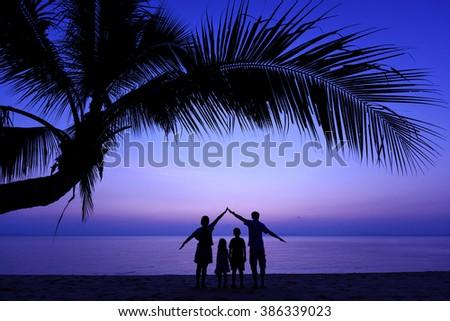 Family with coconut palm tree silhouette at sunset. - stock photo
