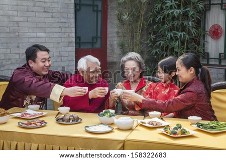 Family with cups raised toasting over a Chinese meal - stock photo