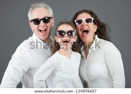 Family with father, mother and daughter. Wearing sunglasses. Studio shot. - stock photo