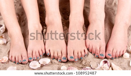 Family with feet in the sand with sea shells - stock photo