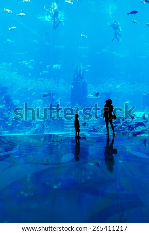 Family with mother and kids observe fish at the big aquarium - stock photo