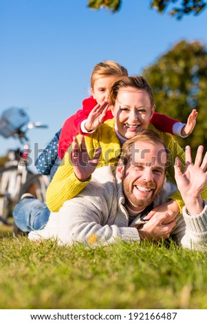 Family with mother, father and daughter having break on family trip with bicycle or cycle in park  - stock photo