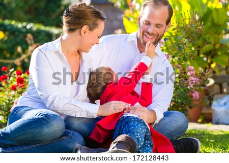 Family with mother, father and daughter together in the garden meadow - stock photo