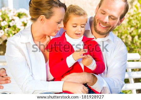 Family with mother, father and daughter together on garden bench in front of home - stock photo