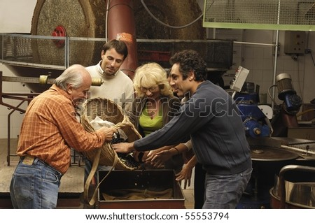 Family with olives in a mill - stock photo