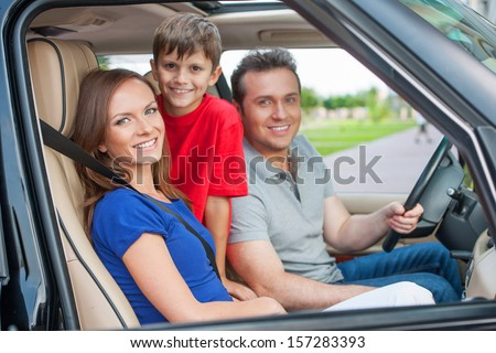Family with one kid is travelling by car, smiling and looking at camera - stock photo