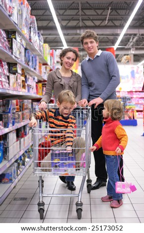 Family with son in cart and little girl in shop, focus on boy - stock photo