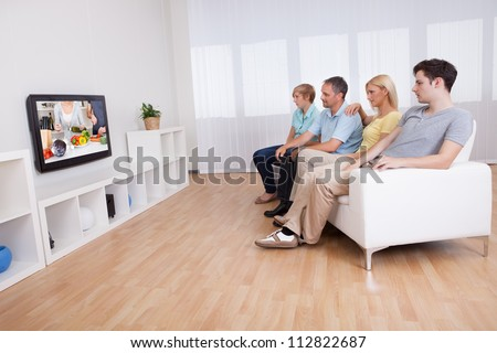 Family with teenage children sitting together on a sofa in the living room watching widescreen television - stock photo