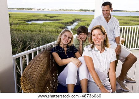 Family with teenager children on vacation sitting together on terrace - stock photo