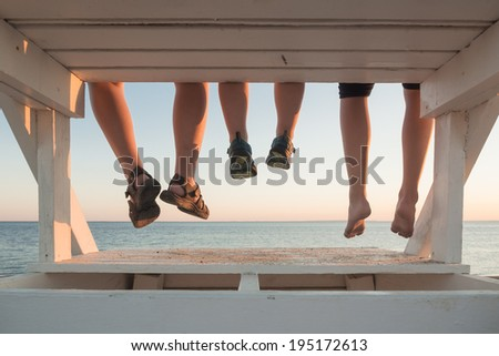 Family with their feet hanging at sunset in Cape Cod - stock photo