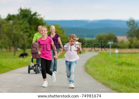 Family with three children (one baby lying in a baby buggy) walking down a path outdoors, two kids are running ahead, there is also a dog - stock photo