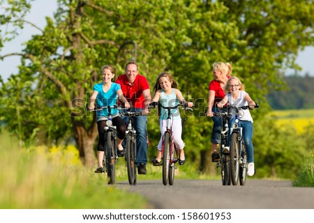 Family with three girls having a weekend excursion on their bikes or bicycles on a summer day in beautiful landscape - stock photo