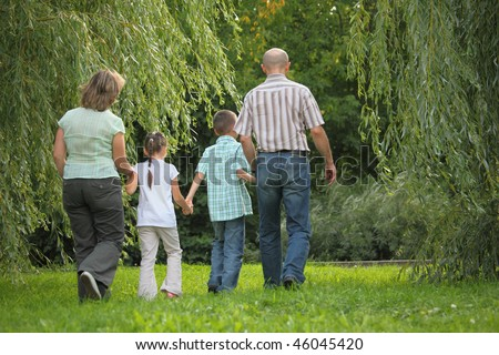 family with two children in early fall park. they are walking away. - stock photo