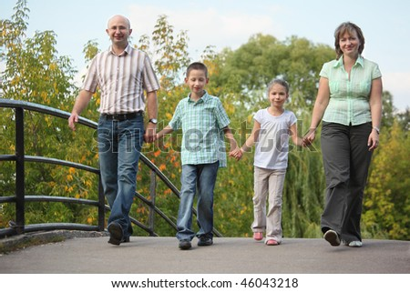 family with two children is walking on bridge in early fall park. family is handies. - stock photo