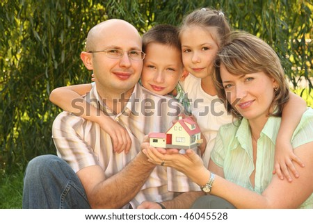 family with two children keeping wendy house in their hands - stock photo