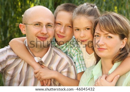 family with two children near osier looking at camera. - stock photo