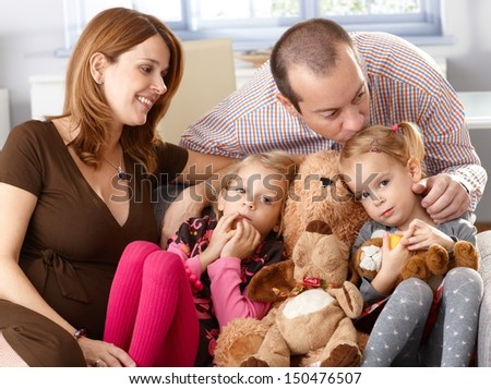 Family with two daughters and pregnant mother sitting on sofa at home, father kissing daughter. - stock photo